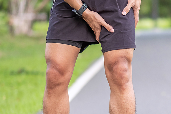 Young adult male with muscle pain during running. runner have leg ache due to Groin Pull.