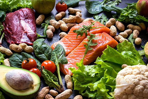 Fresh fish, meat, vegetables, fruits, nuts on black chalk board background. Сauliflower, avocado, apples, tomatoes, salmon, beef, spinach, herbs. Diet/healthy/paleo food. Ingredients for cooking