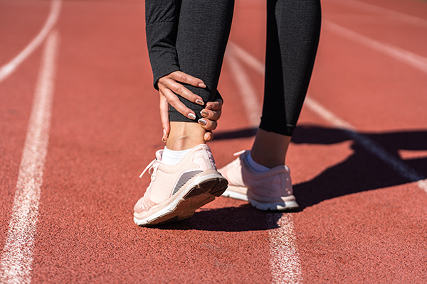 jogger-woman-runner-touching-foot-in-pain-due-to-injury