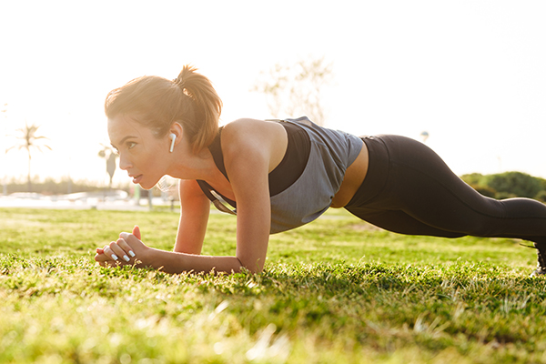 Image of young fitness woman make sport plank exercises outdoors on grass.